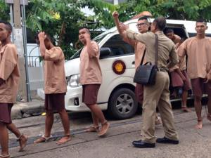 Young democracy activists, shackled and barefooted, being led to a military court